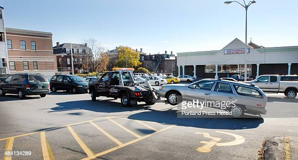 A tow trucks removes a Ford Taurus from the parking lot at 290 Congress St Friday morning October 27 2006 Business owners there have complained that...