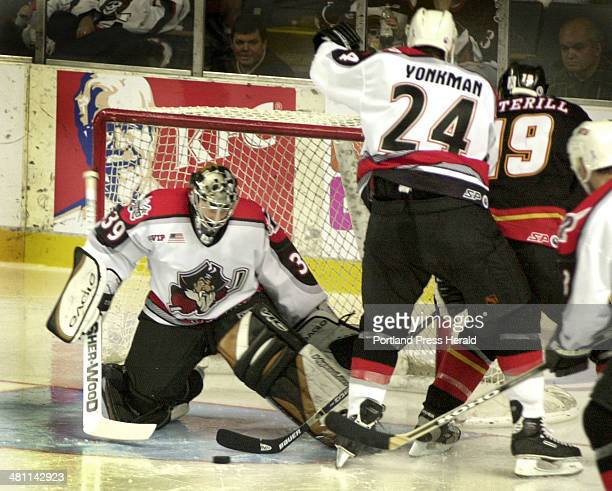 Staff Photo by Jill Brady Sun Dec 02 2001 Pirate's goalie Corey Hirsch keeps an eye on the puck while Nolan Yonkman keeps the pressure on Jason...