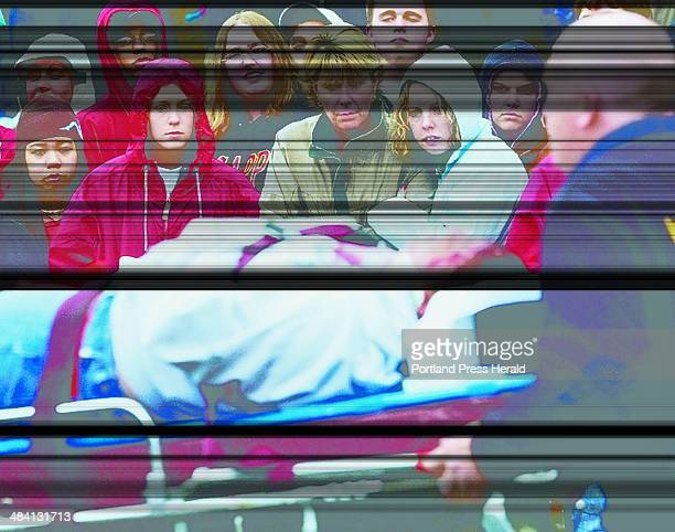 Staff photo by Joe Phelan Cony students and staff watch as Chelsea Clark is wheeled away on a stretcher after a simulated drunken driving accident at...