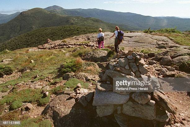 Staff photo BY JOHN EWING Day hikers follow the Appalachian Trail along a ridge on their way to Mount Washington seen in the background Stone cairns...