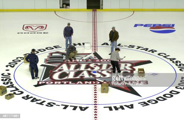 Staff Photo by John Patriquin Tue Jan 28 2003 Workers finish painting the ALL STAR logo at center ice at the Cumberland County Civic Center today for...