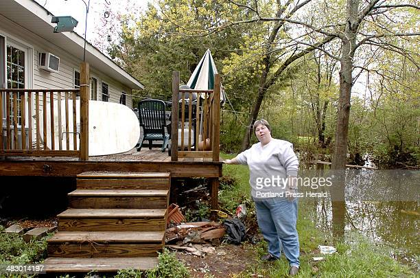 Staff Photo by John Patriquin Tuesday May 16 2006 Carrie Carruth shows where the water level reached the top floor of her deck as waters recede...
