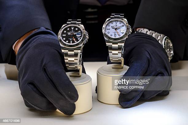 A staff places watches in a display on March 18 2015 at the booth of Swiss watchmaker Rolex during the watch industry's biggest annual trade show...