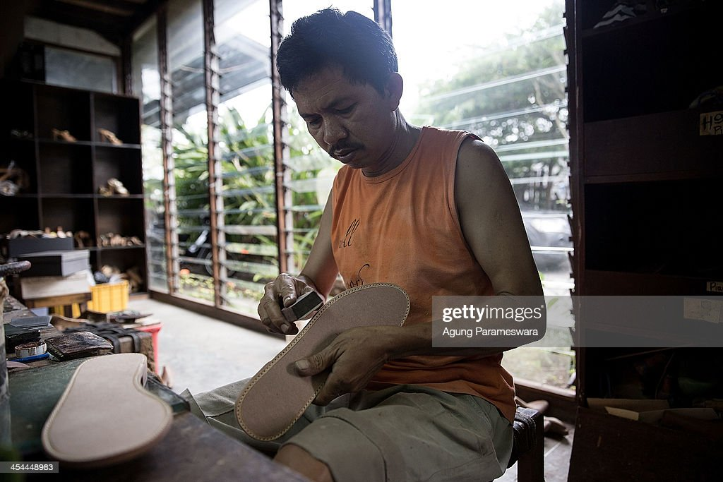 A Staff polishes an insoul part of a shoes at Niluh Djelantik atelier on November 12, 2013 in Canggu Village, Bali, Indonesia. Niluh Djelantik (formerly called Nilou), the hand made high end leather shoe, is produced by Balinese shoe lover and designer Ni Luh Ayu Pertami with 40 shoes designers and workers in a small atelier at Canggu Village. This brand signature by a unique engraving and designed to be comfortable high heels or wedges with elegan touch. Celebrities like Cate Blanchett, Uma Thurman,Julia Roberts ,Paris Hilton, Cameron Diaz and American top model Gisele Bundchen have been known to purchase Niluh Djelantik beautiful shoes and sandals.