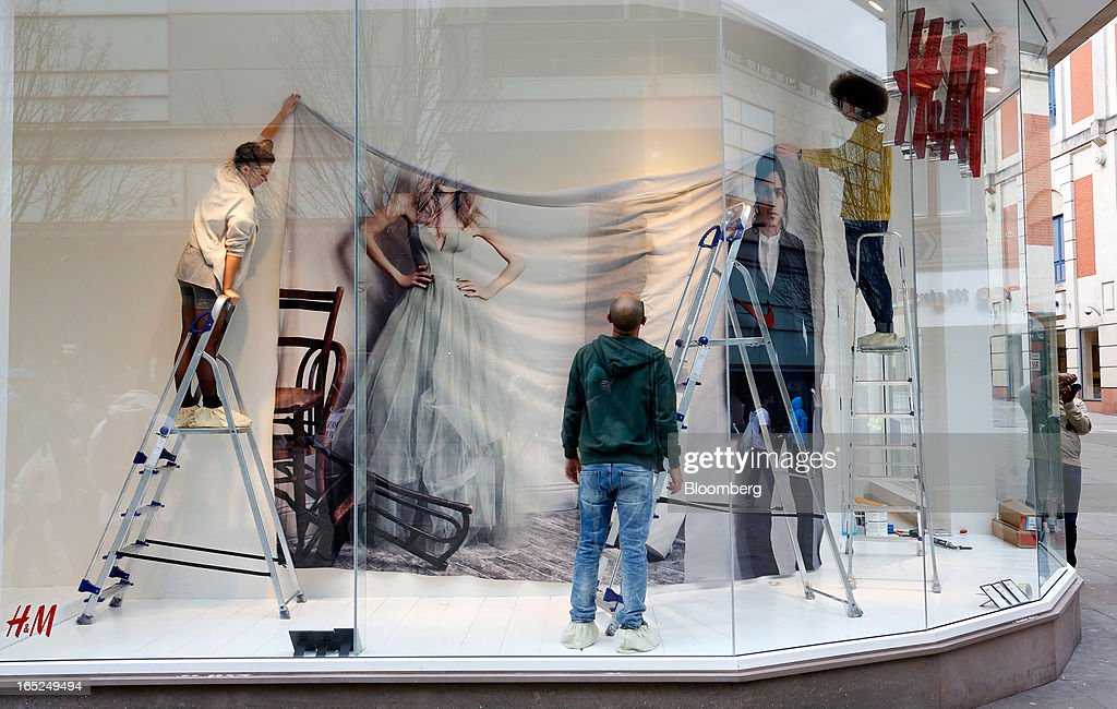 Staff prepare a window display in a Hennes & Mauritz AB (H&M) fashion store in Manchester, U.K., on Monday, April 1, 2013. U.K. retail sales unexpectedly stagnated in March in a sign that consumer spending remains under pressure from higher energy bills and weak wage growth. Photographer: Paul Thomas/Bloomberg via Getty Images