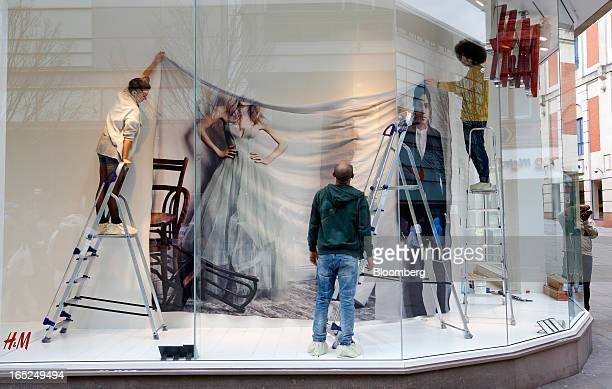 Staff prepare a window display in a Hennes Mauritz AB fashion store in Manchester UK on Monday April 1 2013 UK retail sales unexpectedly stagnated in...