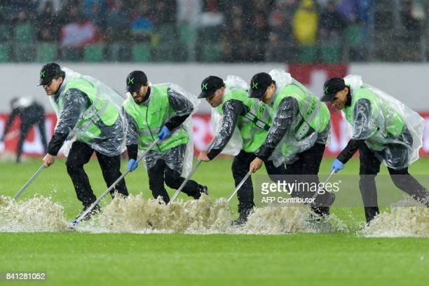 Staff remove water from the field during the break during the FIFA World Cup WC 2018 football qualifier between Switzerland and Andorra at the...