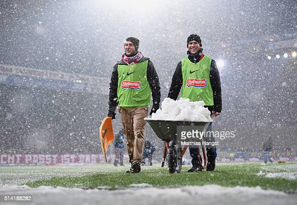 Staff removes snow from the field prior to the Second Bundesliga match between SC Freiburg and RB Leipzig at SchwarzwaldStadion on March 7 2016 in...