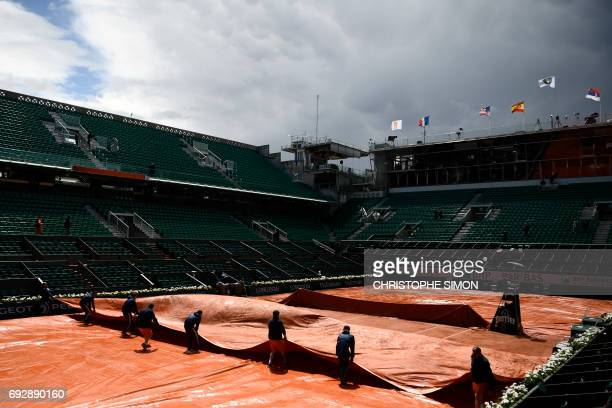 TOPSHOT Staff removes the canvas from the central court after a downpour at the Roland Garros 2017 French tennis Open on June 06 2017 in Paris / AFP...