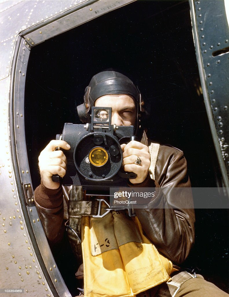 Staff Sargeant Brush poses with his Fairchild K-20 aerial camera at the waist window of a B-17 Flying Fortress bomber, mid-1940s.