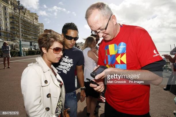 Staff scan digital tickets sent out to Vodafone customers by text message at the Vodafone TBA Concert on Brighton Beach Brighton