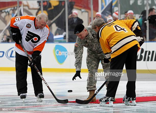 Staff Sergeant Ryan R LaFrance drops the ceremonial first puck for Bobby Clarke honorary captain of the Philadelphia Flyers and Bobby Orr honorary...