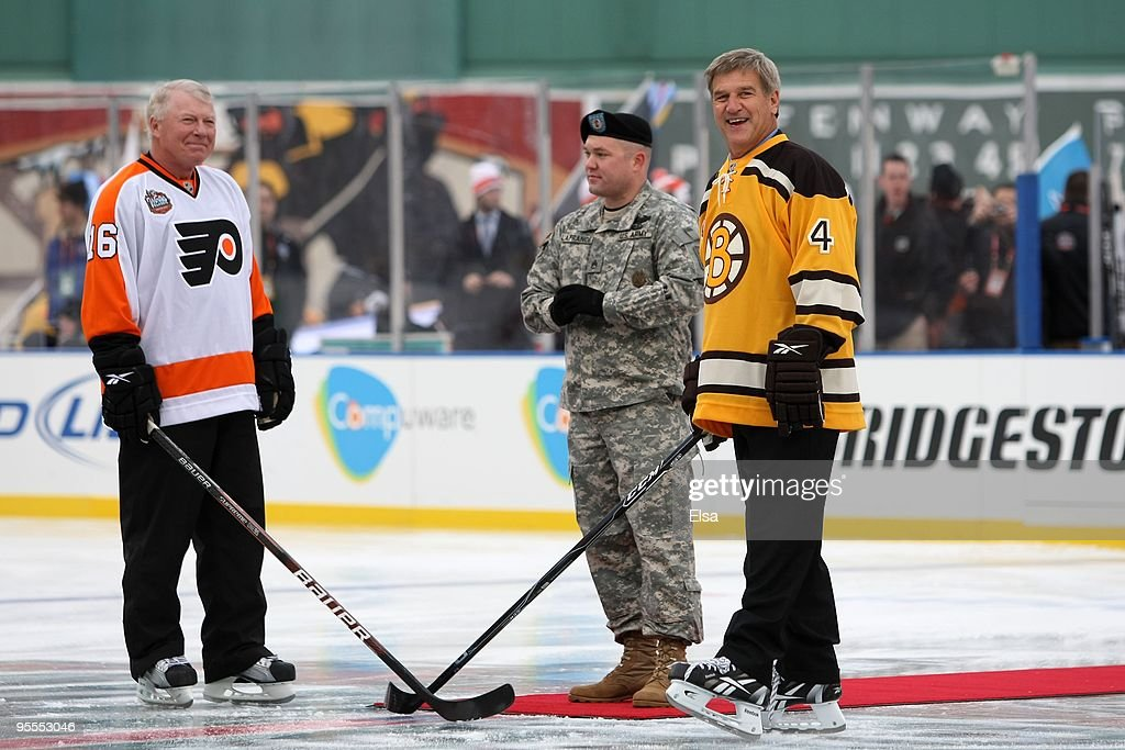 Staff Sergeant Ryan R. LaFrance (C) prepares to drop the ceremonial first puck for <a gi-track='captionPersonalityLinkClicked' href=/galleries/search?phrase=Bobby+Clarke&family=editorial&specificpeople=213882 ng-click='$event.stopPropagation()'>Bobby Clarke</a> #16 (L) honorary captain of the Philadelphia Flyers and <a gi-track='captionPersonalityLinkClicked' href=/galleries/search?phrase=Bobby+Orr&family=editorial&specificpeople=204573 ng-click='$event.stopPropagation()'>Bobby Orr</a> #4 (R) honorary captain of the Boston Bruins during the 2010 Bridgestone Winter Classic at Fenway Park on January 1, 2010 in Boston, Massachusetts.