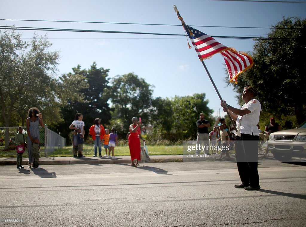 Staff Sergeant Zachary White retired from the Air Force carries the American flag as he participates in a Veterans Day ceremony on November 11, 2013 in Coconut Grove, Florida. The ceremony was held by the Coconut Grove American Legion Post #182 in honor of those veterans who have served the United States.