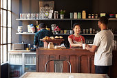 Staff Serving Customer In Busy Coffee Shop