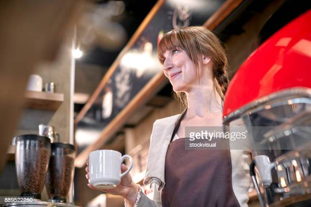 Staff Serving Customer In Coffee Shop