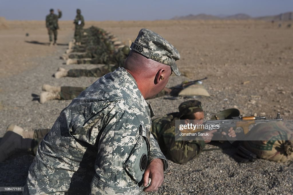 Staff Sgt. David Ward, part of a US military Embedded Training Team (ETT), observes new recruits for the Afghanistan National Army at the firing range November 25, 2008 at Camp Zafar outside of Herat, Afghanistan. The group of 800 recruits are the inaugural class of the training center, which hopes to increase the number of Afghan soldiers in the field, a major goal of coalition forces in Afghanistan.