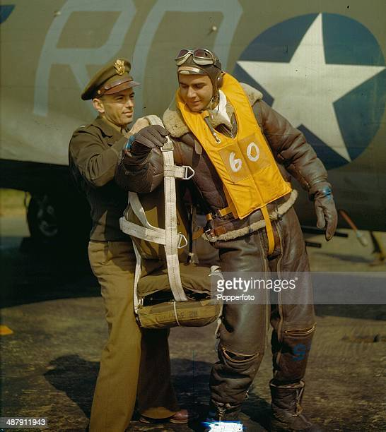 1943 Staff Sgt Frank T Lusic a B17 Flying Fortress gunner wearing his wool lined insulated aviation flying suit is helped on with his parachute prior...
