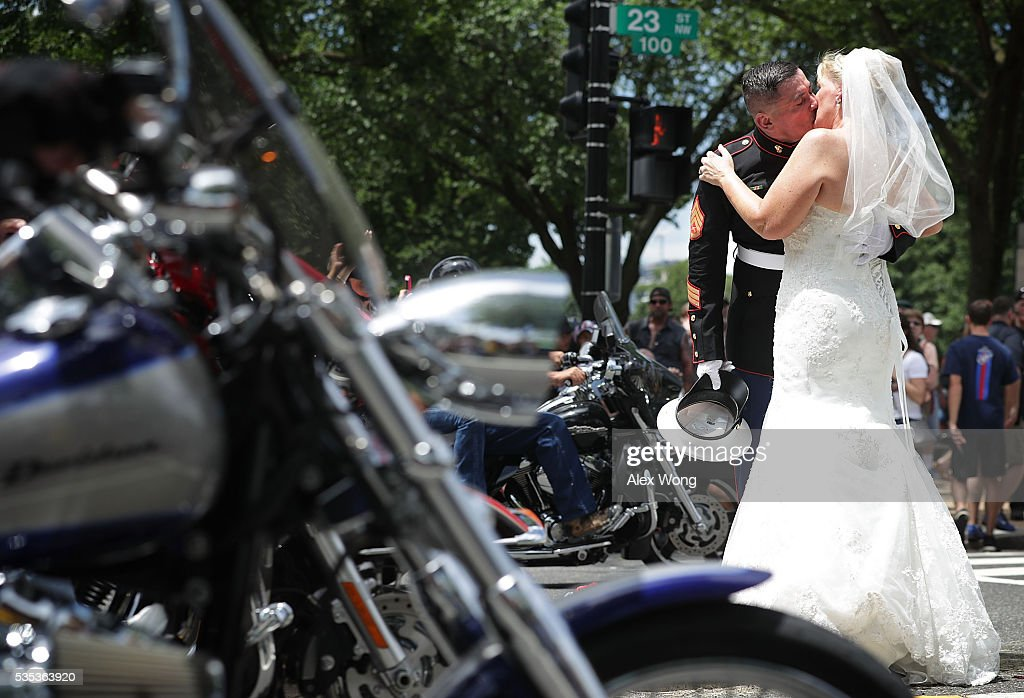 Staff Sgt. Tim Chambers, the saluting Marine, kisses his bride Lorraine Heist during the annual Rolling Thunder First Amendment Demonstration Run May 29, 2016 in Washington, DC. Each year Chambers stands on the route at attention to salute the passing bikers. Bikers are gathering in the annual parade in the nation's capital to remember those who were prisoners of war and missing in action on Memorial Day weekend.