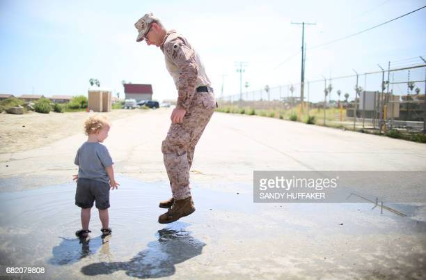 Staff Sgt William Proctor plays in a mud puddle with his son Elijah during a homecoming reception at Camp Pendleton in Oceanside California on May 11...