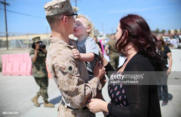 Staff Sgt William Proctor shares a moment with his son Elijah and wife Lindsey upon returning during a homecoming reception at Camp Pendleton in...