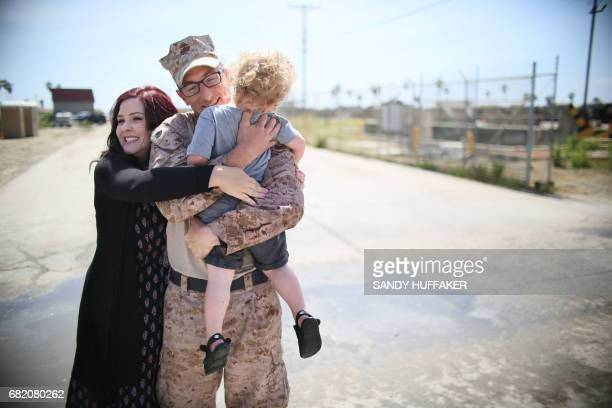 Staff Sgt William Proctor shares a moment with his wife Lindsey and son Elijah upon returning during a homecoming reception at Camp Pendleton in...