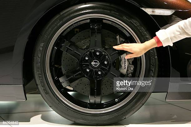 A staff shows the new limitedproduction Nissan GTR SpecV model's forged aluminum wheel and carbonceramic brake at Nissan's headquarters on January 8...