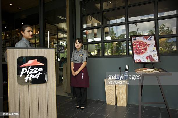 Staff wait for customers outside Pizza Hut's first restaurant in Yangon on October 22 2015 Pizza Hut is to open its first restaurant in Yangon the...
