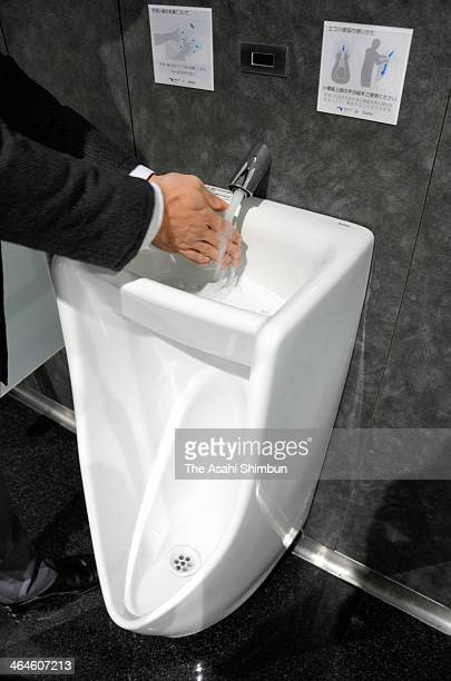 A staff washes his hands at a water basin on the top of a urinal at a toilet of the the Otsu Service Area on the Meishin Expressway on January 8 2014...