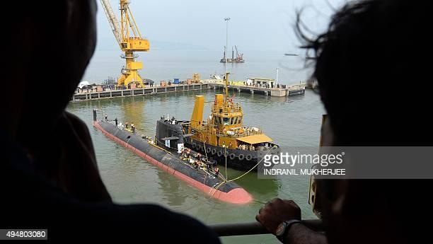 Staff watch from atop a crane as the Scorpene submarine 'Kalvari' cruises into the Naval Dockyard in Mumbai on October 29 2015 'Kalvari' the first...