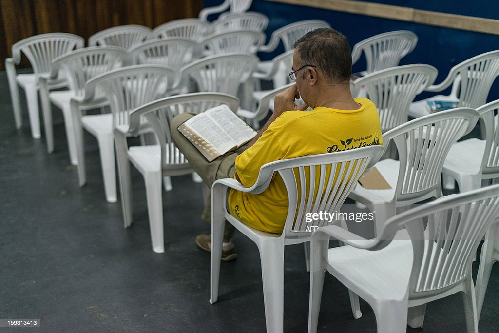 A staff who was drug addicted and homeless of 'Cristolandia', a Christian church offering free breakfasts, lunches, showers or haircuts, reads the Bible, in downtown Sao Paulo, Brazil on January 11, 2013. Former drug users or homelesses work as full time staffs at the church. AFP PHOTO/Yasuyoshi CHIBA