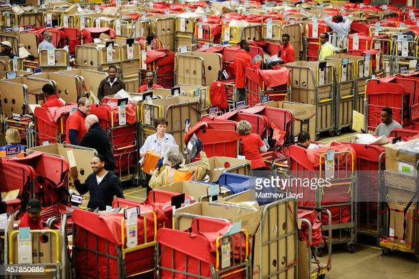Staff work in the packet and parcel section of the Royal Mail's Swan Valley mail centre on December 18 2013 in Northampton England This Friday the...