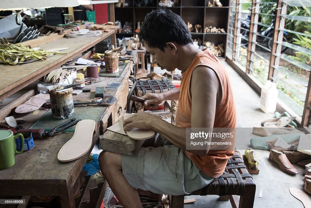 A Staff works make an insoul at Niluh Djelantik atelier on November 12, 2013 in Canggu Village, Bali, Indonesia. Niluh Djelantik (formerly called Nilou), the hand made high end leather shoe, is produced by Balinese shoe lover and designer Ni Luh Ayu Pertami with 40 shoes designers and workers in a small atelier at Canggu Village. This brand signature by a unique engraving and designed to be comfortable high heels or wedges with elegan touch. Celebrities like Cate Blanchett, Uma Thurman,Julia Roberts ,Paris Hilton, Cameron Diaz and American top model Gisele Bundchen have been known to purchase Niluh Djelantik beautiful shoes and sandals.