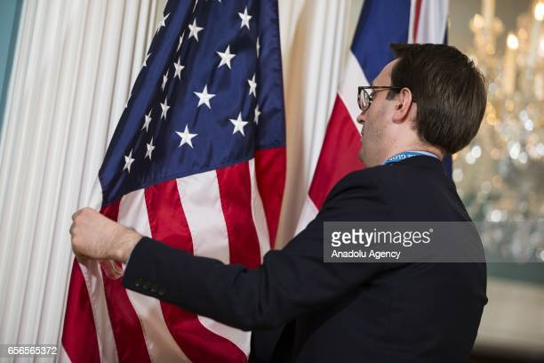 A staffer adjusts the US and UK flags for a photo opportunity with US Secretary of State Rex Tillerson and UK Secretary of Foreign Affairs Boris...