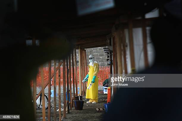A staffer for Doctors Without Borders in protective clothing stands in a highrisk area of the MSF Ebola treatment center on August 21 2014 near...