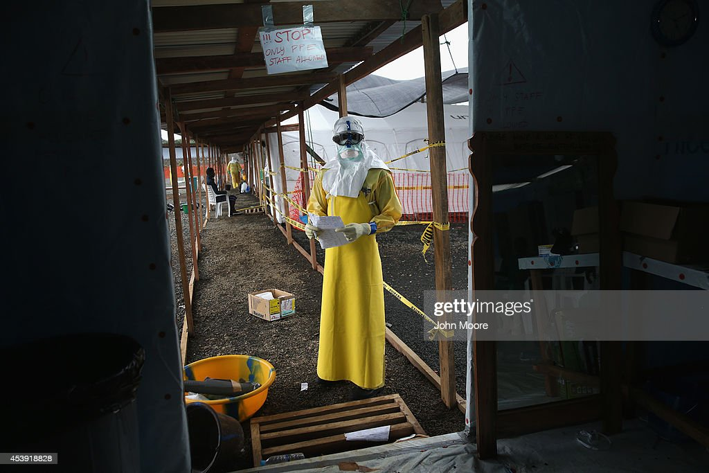 A staffer for Doctors Without Borders (MSF), stands in protective clothing in the high risk area of the new MSF Ebola treatment center on August 21, 2014 near Monrovia, Liberia. The MSF center has 120 beds and is being expanded, making it the largest Ebola treatment center in history. The Ebola epidemic has killed more than 1,200 people in West Africa.