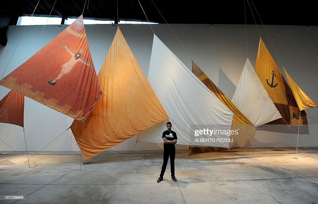 A staffer poses in front of 'Painted Sails' by Jannis Kounellis on May 28, 2010 in one of the new exhibition halls at the MACRO, Museum of Contemporary Art of Rome (Museo d'Arte Contemporanea Roma), designed by French Odile Decq during press a preview in Rome .