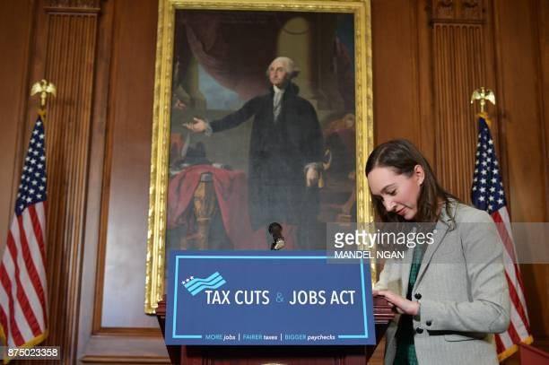 A staffer puts up a sign in preparation for a press conference after the House passed its version of the Republican tax overhaul in the Rayburn Room...