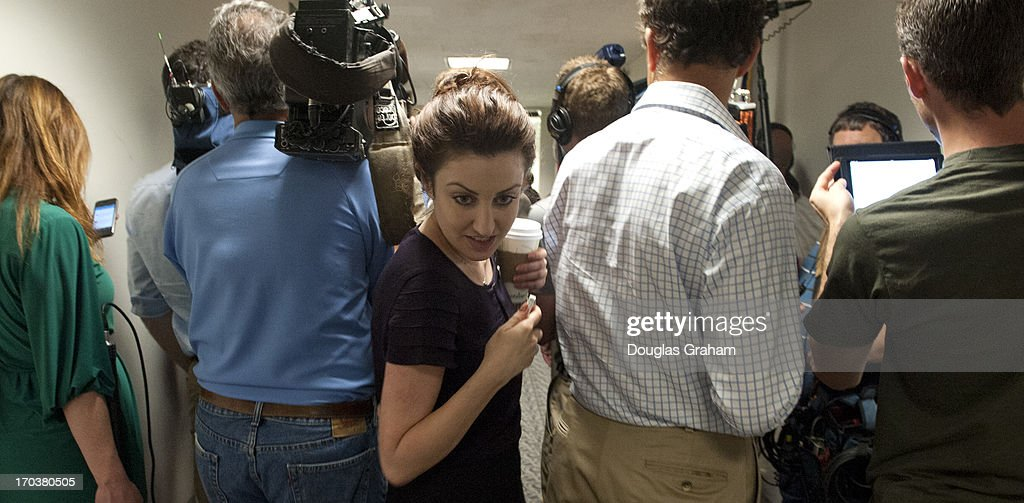 A staffer squeezes through TV crews as they clog the hallway outside Sen. Joe Manchin, D-WVA., office as they wait to cover a press conference with the Newtown families of the Sandy Hook shooting victims in the Hart Senate Office Building on June 12, 2013.