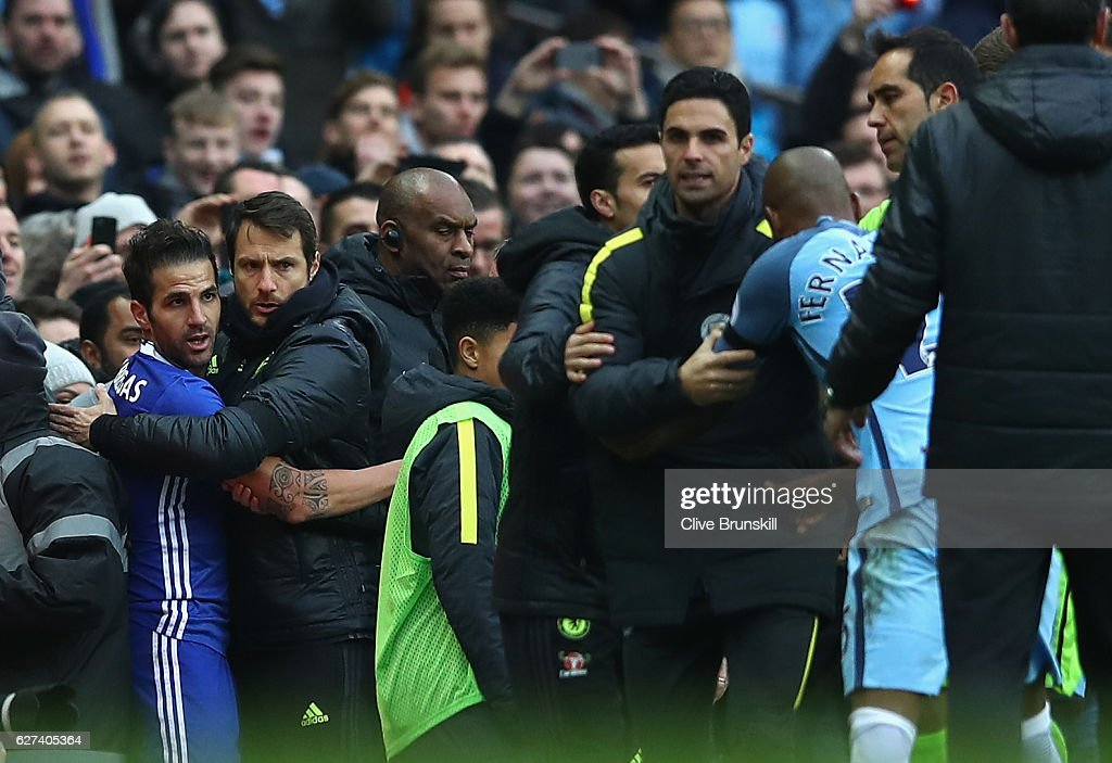 Staffs and offiicials try to separate Fernandinho of Manchester City and Cesc Fabregas of Chelsea after Fernandinho pushes down Fabregas during the Premier League match between Manchester City and Chelsea at Etihad Stadium on December 3, 2016 in Manchester, England.