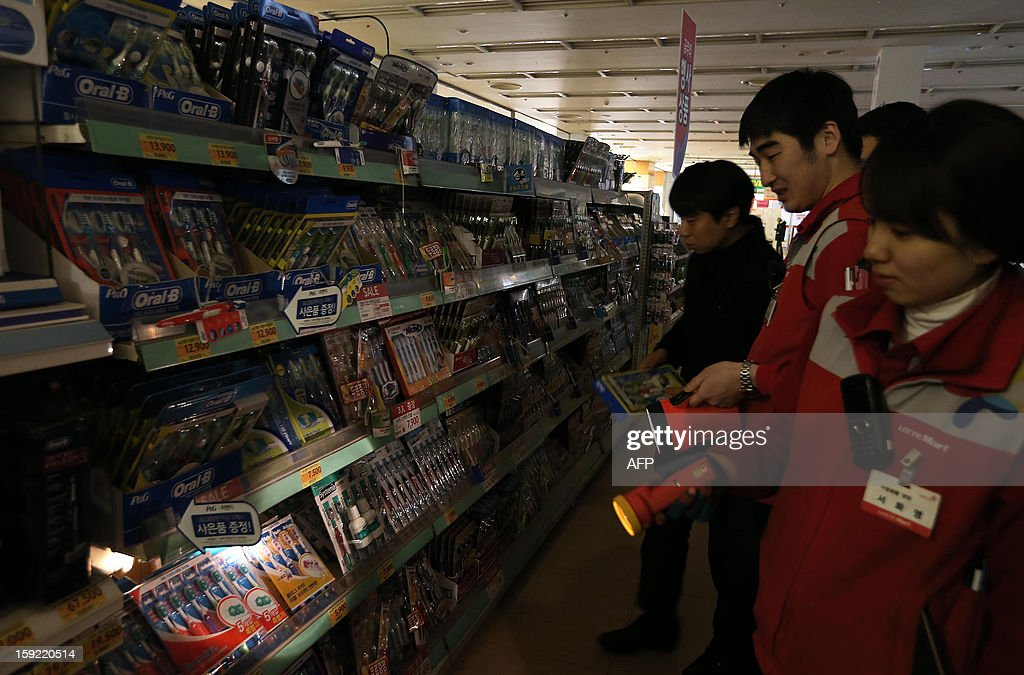 Staffs check a darken discount store after the lights were turned off during a national drill in the case of an emergency power blackout in Seoul on January 10, 2013. Sirens sounded across South Korea and subway systems grounded to a halt as the government held a national drill aimed at averting a countrywide power blackout. REPUBLIC