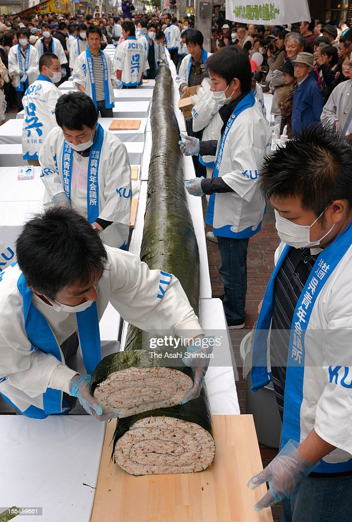 Staffs cut the long sushi roll, 21-meter-long and almost 30-centimeter diameter, during an event on November 4, 2012 in Kure, Hiroshima, Japan. The roll is made to commemorate the warship Yamato, that was built in Kure and sunk on the way to Okinawa during the WWII. tried to make the same size as Yamato's main cannon.