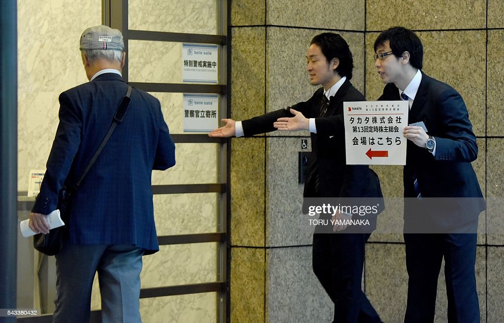 Staffs lead a shareholder (L) of crisis-hit airbag supplier Takata to the venue of a shareholders meeting in Tokyo on June 28, 2016. The Japanese car parts maker Takata held the 13th ordinary shareholders meeting following the global recall of several automakers caused by defect of the company's airbags. / AFP / TORU