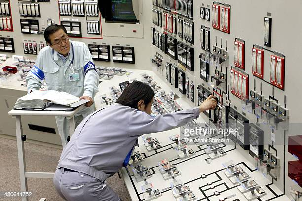Staffs of the Kyushu Electric Power Co's Sendai Nuclear Power Plant check the procedures ahead of the reactor restart at a mock control room on July...