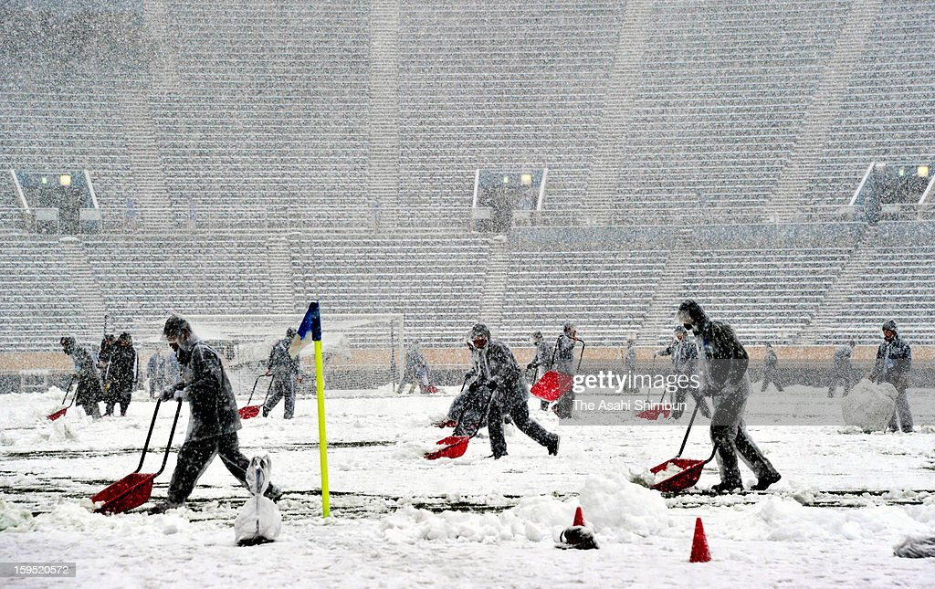 Staffs try to remove snow on the pitch in preparation for the All Japan High School Football Championship Final at the National Stadium on January 14, 2013 in Tokyo, Japan. The match was postponed. A strong low pressure system caused heavy snow and strong wind in the coast area including Tokyo, more than 500 injured.