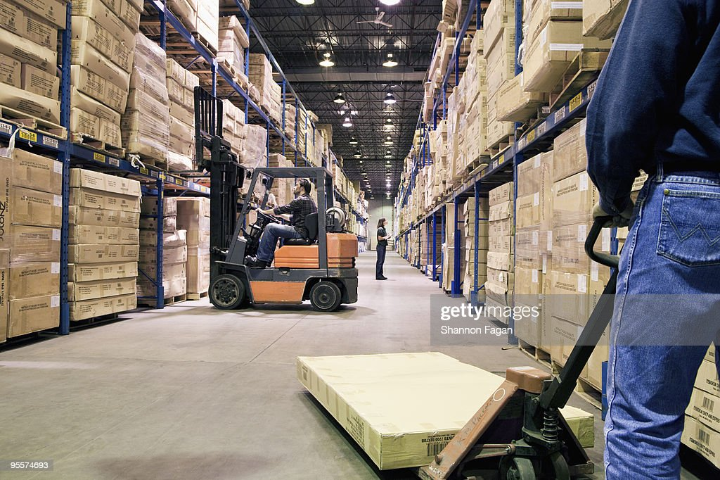 Staffs working different tasks in a warehouse : Stock Photo