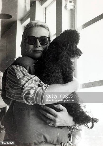 April 1956 American actress Grace Kelly with her poodle Oliver as they wait for lifeboat drill on board the liner 'Constitution' on the journey to...