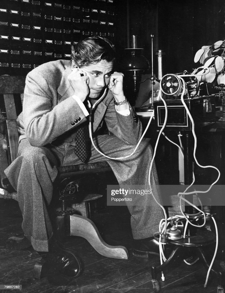 circa 1942 American actor Glenn Ford who played the title role in the fim 'Adventures of Martin Eden' pictured listening to to the voice of the...