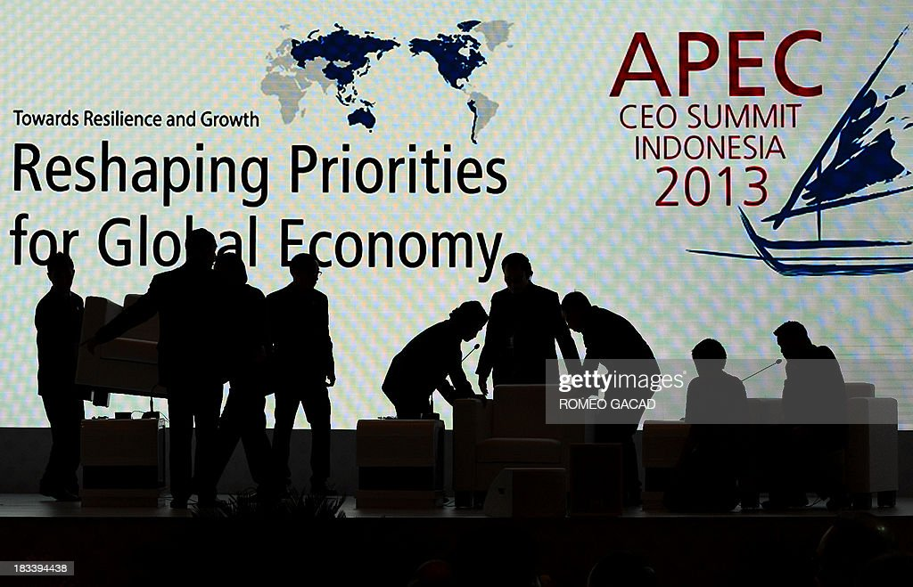 Stage assistants are silhouetted as they adjust the furniture between speakers at the Asia-Pacific Economic Cooperation (APEC) CEO Summit attended by leaders of APEC member countries and top international business executives in Nusa Dua on the Indonesian resort island of Bali on October 6, 2013. Leaders of the 21-member APEC grouping are arriving in Bali ahead of the leader's summit on October 7-8.
