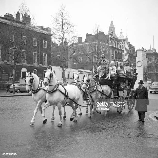 A stage coach flying the flag of St George travels along Whitehall during St George's Day celebrations On the box is a tophatted driver and 50 women...